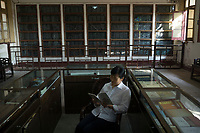 Huanggang, Hebei province, China - A shopkeeper reads a book about Su Dongpo against a backdrop of ancient tablet inscriptions of poems by famous Song dynasty poet and politician Su dongpo at Dongpo Red Cliff, October 2014.