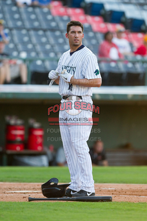 Travis Ishikawa (14) of the Charlotte Knights removes his batting gloves after having made the third out of the first inning against the Indianapolis Indians at Knights Stadium on July 22, 2012 in Fort Mill, South Carolina.  The Indians defeated the Knights 17-1.  (Brian Westerholt/Four Seam Images)