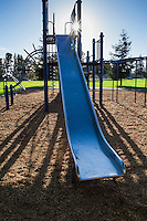 A blue slide at a city park playground with a sunburst shining at the top of the slide.
