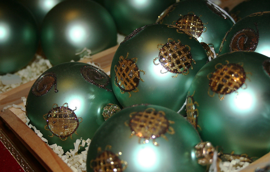 Teal colored holiday ornaments in storage box with packing paper
