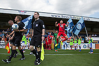 Russell Penn of York City leaps in the air as Referee Oliver Langford  and his officials lead the teams out during the Sky Bet League 2 match between Wycombe Wanderers and York City at Adams Park, High Wycombe, England on 8 August 2015. Photo by Andy Rowland.