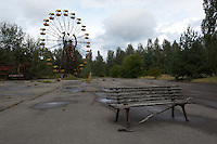 The Ferris wheel at the amusement park in Pripyat. <br /> The brand new park was planned to be opened to the public during the celebrations on May 1, 1986, but disaster struck first.<br /> Pripyat was built 1970 as a modern city for personnel at the Chernobyl Nuclear Power Plant a couple of kilometers south. After the nuclear disaster at reactor 4 on April 26 1986, the town's 48.000 inhabitants was evacuated to other parts of the country. Pripiat is today a radioactive ghost town. The whole area is contamined with nuclear material, the half-life of plutonium-239 is more than 24.000 years.<br /> Pripyat, Ukraine.<br /> August 2008.