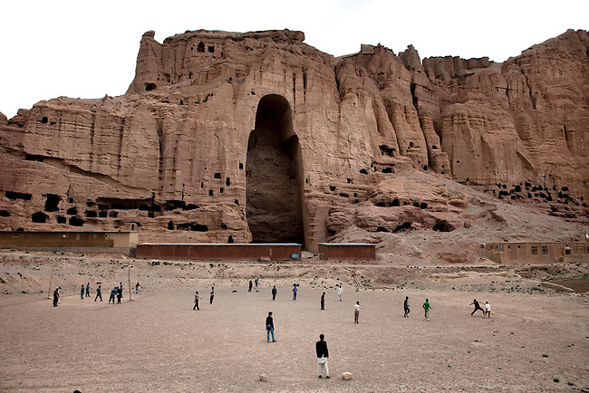 08 May 2012, Bamiyan, Afghanistan :  Locla children play football in front of the empty niches that once contained the largest free standing statues of Buddha in the world  that dominate the skyline of Bamiyan city. The Taliban destroyed the statues by blowing them up in March 2001 . Picture by Graham Crouch/World Bank