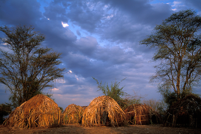 Traditional huts in a Mursi village protect the villagers from the oncoming storm, in Ethiopia's Omo river region.