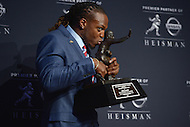 New York City, NY - December 12, 2015: University of Alabama running back Derrick Henry kisses the Heisman memorial Trophy during a press conference at the New York Marriott Marquis hotel after winning the 2015 Heisman, December 12, 2015. Henry rushed for 1,986 yards, averaging 152.8 yards per game, breaking the single season SEC rushing record held by 1982 Heisman winner Herschel Walker. (Photo by Don Baxter/Media Images International)