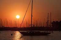 The rising sun turns the sky orange over sailboats and other pleasure craft docked in the harbor in Annapolis, Maryland.
