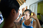 A woman gets headphones placed on her head as a group of university students learn about disability by having individual disabilities imposed on them during a sensitivity training session at Piña Palmera, a community based rehabilitation program in Zipolite, a town in Oaxaca, Mexico.