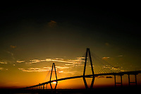 The setting sun silhouettes Charleston, SC's, Cooper River Bridge, also called the Arthur Ravenel Jr. Bridge. The cable-stayed bridge connects downtown Charleston to Mount Pleasant, SC. It was designed by Parsons Brinkerhoff.