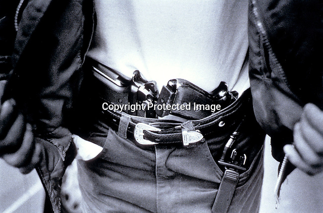 DIPOLIC00096.Police. An undercover police officer on November 22, 1998 showing his arms outside a shop in central Johannesburg, South Africa. A suspected burglar was caught and arrested by the police; guns. .©Per-Anders Pettersson/iAfrika Photos