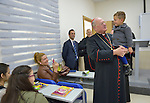 Cardinal Timothy Dolan, archbishop of New York and chair of the Catholic Near East Welfare Association, holds one student's son as he talks with students in a class in the Catholic University in Ankawa, near Erbil, Iraq, on April 11, 2016.