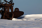 Wind blown snow formes on the lee side of an old farm plow, an Iowa winter.