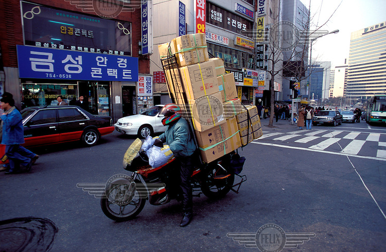© Jim Holmes / Panos Pictures..Seoul, SOUTH KOREA..Motorbike laden down with goods in the city centre..