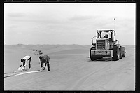 Chinese workers construct a highway in the Tengger Desert, Inner Mongolia, China, 2015.