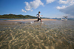 A male tourist runs through the tropical water at a sandbar island near El Nido, in the famous and beautiful Bacuit Archipelago in Palawan, Philippines.