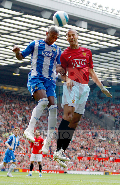 Rio Ferdinand of Manchester United challenges Marcus Bent of Wigan Athletic