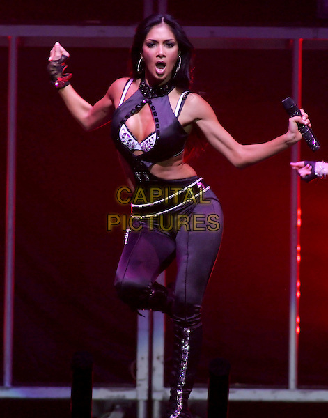 NICOLE SCHERZINGER of THE PUSSYCAT DOLLS.The Pussycat Dolls perform live to a sold out crowd as the opening act for Christina Aguilera during her Back To Basics Tour at The Honda Center in Anaheim, California on March 05 2007..full length on stage  concert gig black microphone dancing legs crossed funny arms.CAP/EAS.©Eastman/Capital Pictures