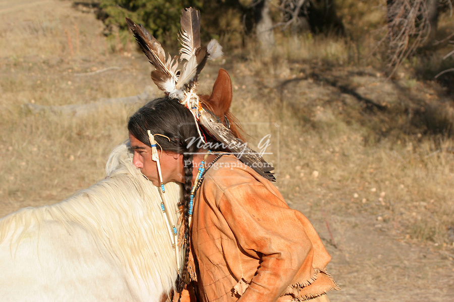A Native American Indian man kissing his horse