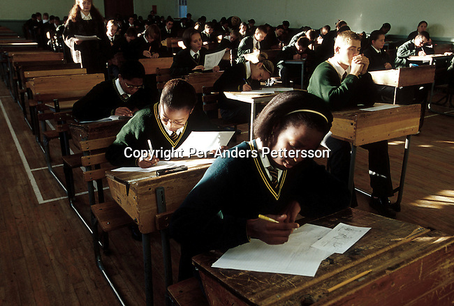 Black and white students writing exams alongside on June 21, 2001 at Vryburg Highs School in Vryburg, South Africa. Vryburg, a small and very conservative farming town about 400 km west of Johannesburg has had a lot of high profile racist attacks since the democratic elections in 1994. A black boy is currently in prison after stabbing a white boy in Vryburg High School.The school has had a problem with  the integration of the black pupils in the former only white school. South Africa is still battling racism after seven years of a democraticly elected black government. (Photo: Per-Anders Pettersson)