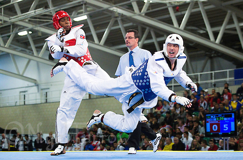 04 MAY 2012 - MANCHESTER, GBR - Lutalo Muhammad (GBR) of Great Britain (on left in red) battles with Nikola Bojo (CRO) of Croatia (on right in blue) during their men's -87kg category quarter final contest at the 2012 European Taekwondo Championships at Sportcity in Manchester, Great Britain (PHOTO (C) 2012 NIGEL FARROW)