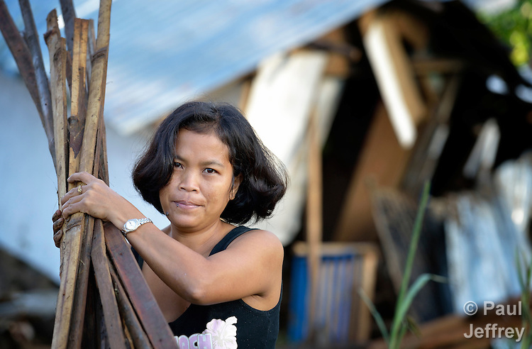 The day after Typhoon Bopha raged through the southern Philippines island of Mindanao, Maravic Tinhay cleans up the rubble of her home, damaged by flood waters, in Cagayan de Oro.