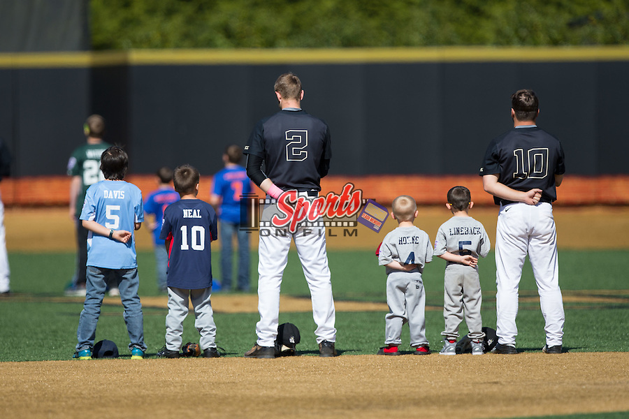 Johnny Aiello (2) and Nate Mondou (10) of the Wake Forest Demon Deacons are joined on the field by several youth baseball players for the National Anthem prior to the game against the Florida State Seminoles at David F. Couch Ballpark on April 16, 2016 in Winston-Salem, North Carolina.  The Seminoles defeated the Demon Deacons 13-8.  (Brian Westerholt/Sports On Film)