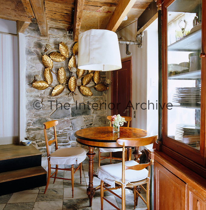 A brass leaf sculpture overlooks a small Biedermeier dining table and chairs in a corner of the kitchen