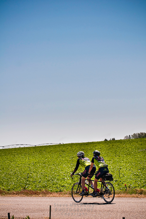 Touring cyclists on tandem bicycle, biking along a rural road in Southern Idaho.