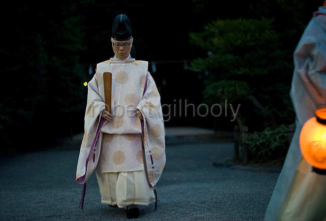 Head priest Shigeho Yoshida (left) is led through the shrine grounds during the annual Reitaisai Grand Festival at Tsurugaoka Hachimangu Shrine in Kamakura, Japan on  14 Sept. 2012.  Sept 14 marks the first day of the 3-day Reitaisai festival, which starts early in the morning when shrine priests and officials perform a purification ritual in the ocean during a rite known as hamaorisai and limaxes with a display of yabusame horseback archery. Photographer: Robert Gilhooly