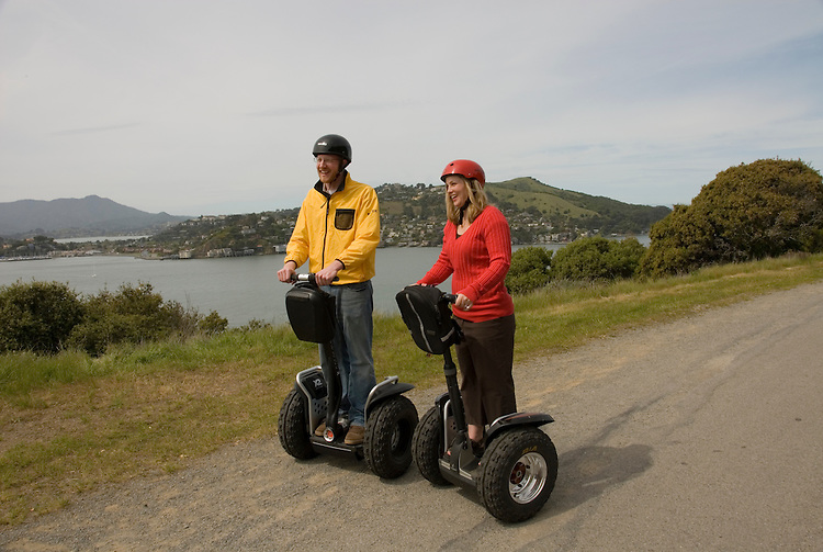 Couple on Segways, each on a Segway, on Angel Island State Park in San Francisco Bay, California, CA. Model released..Photo camari210-70403..Photo copyright Lee Foster, www.fostertravel.com, 510-549-2202, lee@fostertravel.com.