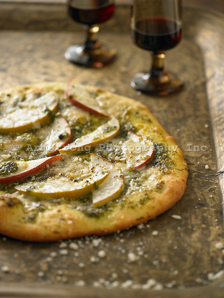 A pizza topped with pears on a pesto base.
