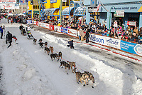 Pete Kaiser runs down 4th avenue leaving the start line during the Ceremonial Start of the 2016 Iditarod in Anchorage, Alaska.  March 05, 2016