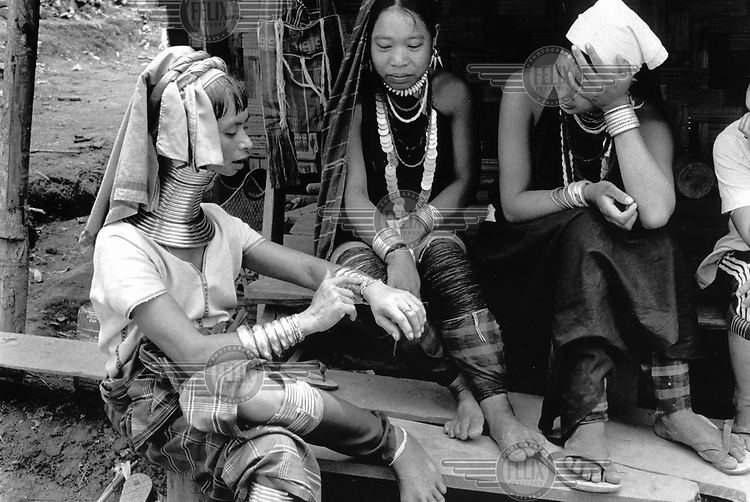 Nu Pu Ah refugee camp, Mae Hong Son province, Thailand. A Kayan woman shows her jewellery to Kayah women who are visiting the village because they have never seen the longneck people before.