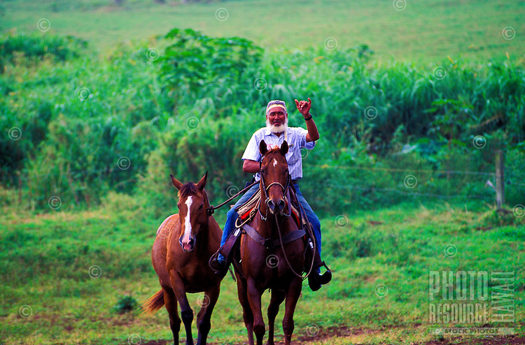 Sonny gives the shaka sign (a Hawaiian hand gesture meaning Hang Loose, Hi or Aloha) as he brings in the horses at the end of the day at Hana Ranch.
