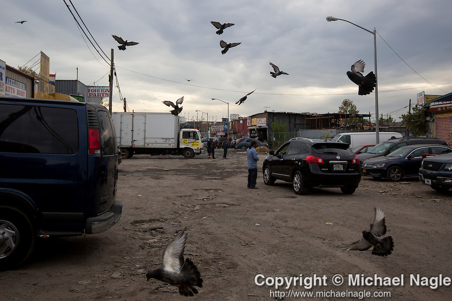 QUEENS, NY -- OCTOBER 22, 2013:  A worker talks with a passing car in Willets Point on October 22, 2013 in Queens.  Photographer: Michael Nagle for The New York Times