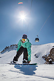 USA, California, Mammoth, a snowboarder strapping in after getting off the lift at Mammoth Ski Resort