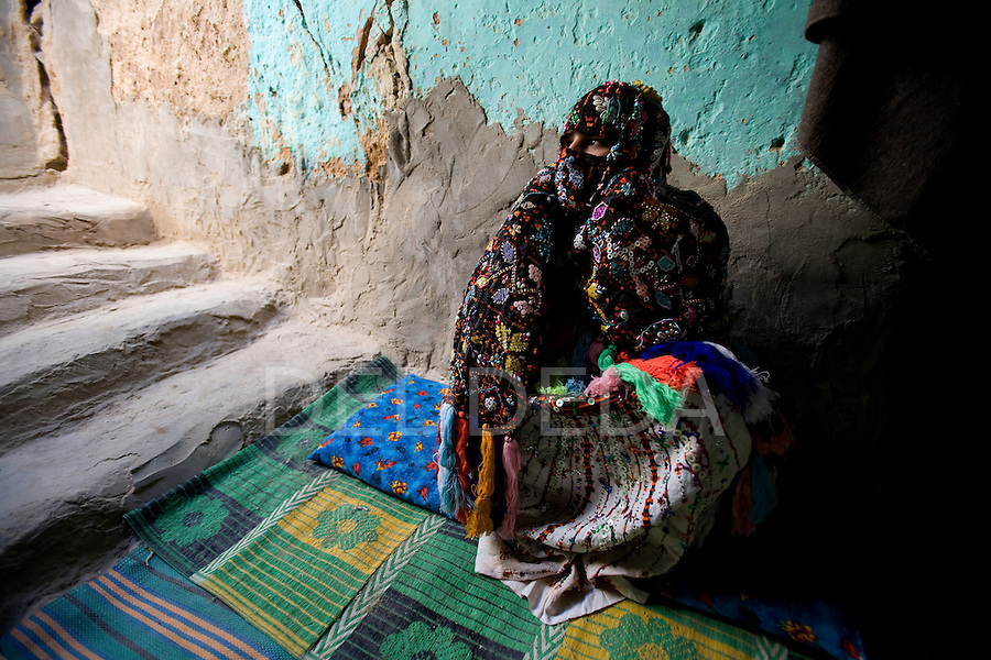 A local Siwan woman dressed in hand-made traditional clothing sits inside her home in Siwa Town of the Siwa Oasis, Egypt.