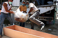 Tyr, Lebanon, July 21 2006.More than 80 Israeli bombardment victims' bodies have been kept in refrigerated trucks for several days by the Lebanese authorities to allow for identifications before being put in coffins labeled with their names and details to be buried in a mass grave nearby. Putting the bodies in their coffins proves a gruesome task as many victims are simply not recognizable, their bodies reduced to mere fragments by the power of the israeli bombs.