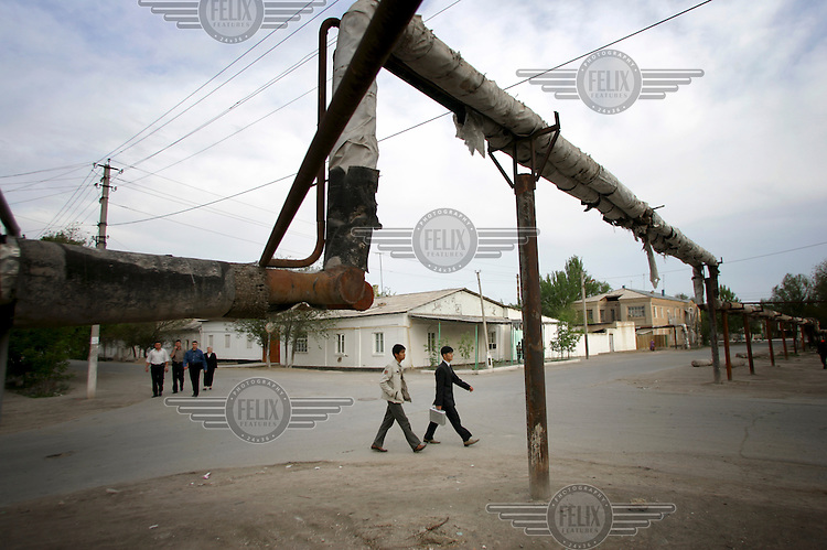 People walk beneath a gas pipe lining a road in Nukus.