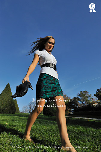 Woman walking barefoot on grass, shoes in hand (Licence this image exclusively with Getty: http://www.gettyimages.com/detail/84430584 )