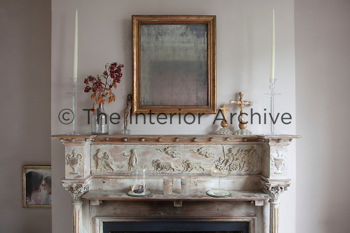 A foxed mirror hangs above the living room mantelpiece, dressed simply with religious ornaments and dried flowers