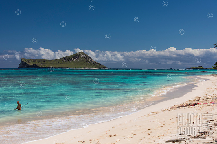 Beachgoers enjoy the warm white sand and turquoise water of Waimanalo Beach, with Manana and Kaohikaipu Islands (or Rabbit and Bird Islands) in the distance, Windward O'ahu.