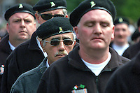 Brendan Hughes, second from front in dark glasses, beret, and with moustache, marches with D Company IRA in a parade on the Falls Rd, Belfast, N Ireland, on 24th June 2001. 20010624001BH.<br />
