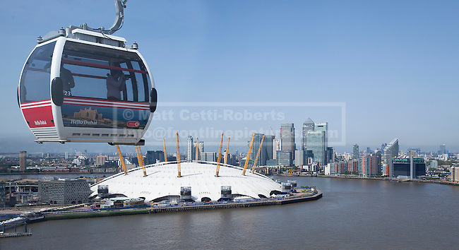 28/06/2012. LONDON, UK. An Emirates Air-Line cabin is seen with the O2 Dome, and Canary Wharf beyond, at the launch of London's first cable car system today (28/06/12). The new cable car system, running across the River Thames between the Greenwich Peninsula and the Royal Docks in East London, was today opened to the public, despite fears that it would not be ready in time for the London 2012 Olympics. Photo credit: Matt Cetti-Roberts