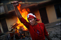 A pro-democracy protester grip's a looted police batton while furniture from a government office burns behind him in Kathmandu, Nepal on 21 April, 2006. Tens of thousands of pro-democracy protesters defied curfew orders and a ban on political demonstrations to rally against King Gyanendra's absolute rule.<br />