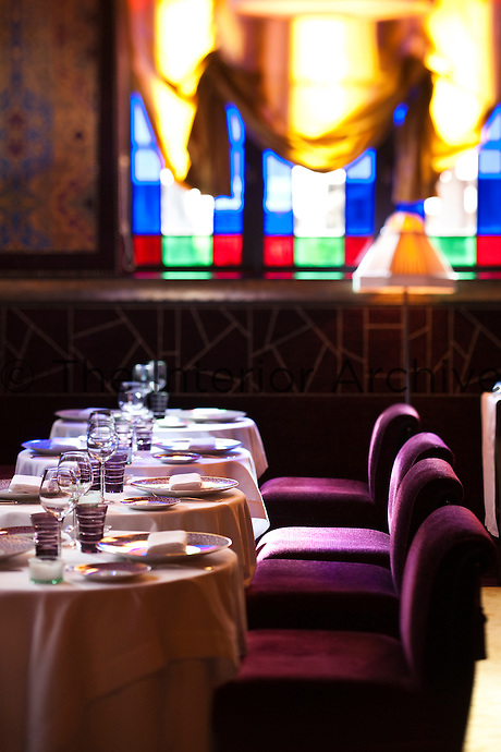 The dining room with a row of laid tables and a colorful stained glass window