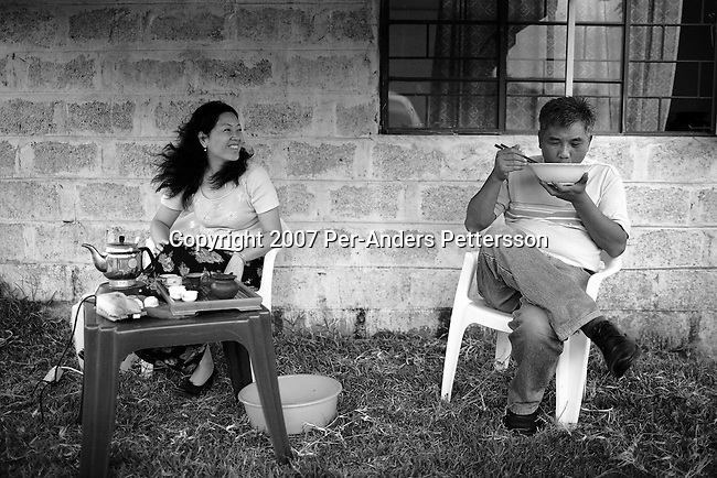 NDOLA, ZAMBIA MARCH 24: Mr. Chen Ting Hui, age 48, eats his lunch as his wife Liang Jin Jie, age 41, looks at him on March 24, 2007 in Ndola, Zambia. Mr. Hui is a General Manager for Eastern Union Limited, a China based company that buys Copper from Congo DRC, and brings it to Ndola to their Copper smelter. The smelter was shipped from China and operates 24 hours a day in an Industrial area in Ndola. The copper is eventually trucked to Dar es Salaam in Tanzania and on ships to China. Tens of thousands of Chinese has come to Africa the last years to work in infrastructure projects and businesses. Chinese companies are often the lowest bidders for contracts, pricing out the more expensive European companies. The Chinese people often live where they work and rarely interact with the local population. Most Chinese don't speak English and they are mostly staying in the compounds cooking their Chinese food, and watching Chinese Television and DVDs. (Photo by Per-Anders Pettersson)....