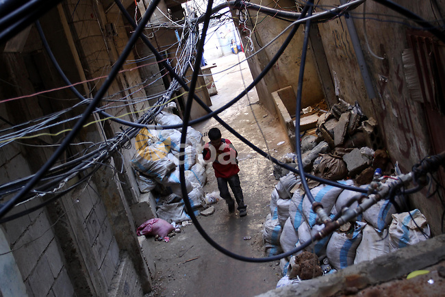 Palestinians walk in alley in one of the most poor regions at Sabra and Shatila Palestinian refugee camp in Beirut, in Lebanon, March 5, 2012. About 11,000 person live in this poor refugee camp who face hard and difficult life. Photo by Mohammed Asad