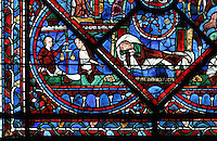 Joseph's dream, a sleeping Joseph dreams of the sun, moon and 11 stars, representing his parents and brothers, and to the left, the donor window of money lenders, shown weighing out gold coins, from the Life of Joseph stained glass window, 13th century, in the nave of Chartres cathedral, Eure-et-Loir, France. Chartres cathedral was built 1194-1250 and is a fine example of Gothic architecture. Most of its windows date from 1205-40 although a few earlier 12th century examples are also intact. It was declared a UNESCO World Heritage Site in 1979. Picture by Manuel Cohen