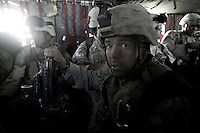 A US ARMY soldier from battle company, 2nd battalion, 503d regiment, 173d airborne brigade sits on a over packed with personnel chinook helicopter after spending 24 hours in the village of Zinde, in the kak afghan district, zabul province of southern afghanistan on september 06 2005..US intelligence had spotted 12 taliban in the village of Zinde. After 4 hours of intense exchange of fire and use of air support Apache gunships and A10 aircrafts 08 talibans were killed, one was captured and one ran away..On September 06 the same unit was moved to a different location where a Taliban commander, N16 on the US most wanted list for Afghanistan was supposed to be hiding. He was not found. In the afternoon the unit was moved to the village of Kawati Atis where a stash of weapons was supposed to be hidden in a compound. The raid lasted for 5 hours, involving a 3km movement trough a valley. The unit occupied the compound and spent the night in it. The weapons, mostly mortar ammunitions used to attack US bases in the region where not found..The next morning, on September 07 two squads where sent to find Taliban observation posts that were following US movements in the village. The unit then  attacked with mortars  the observation points in a hill close to the compound..The Unit was extracted by Chinook helicopters and brought back to the Lagman forward operating base on late afternoon of the same day.