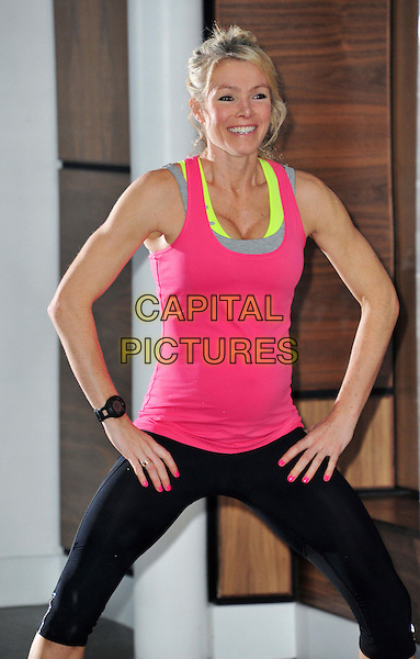 Nell McAndrew  .Glamour model and fitness expert launches her fifth DVD 'Peak Energy Recharged', Jumeirah Carlton Tower, London, England..November 6th, 2012.exercise half 3/4 cleavage length yellow tank vest top pink black spandex smiling leggings  squats gesture  pregnant .CAP/BF.©Bob Fidgeon/Capital Pictures.